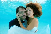 The groom holds his bride in his arms under the water, Indian Ocean, Maldives.