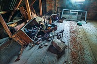 Up in the attic. Old boxes, bottles and other junk under a thick layer of old dust. Sunbeam shining through a window.