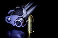 Black gun and bullets on a black background.