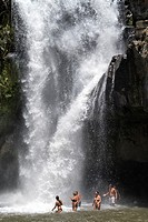tourists enjoying a bath in the Tegenungan waterfall near Ubud, Bali, Indonesia
