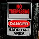 No trespassing hard hat area sign.
