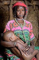 Portrait of a Mbororo woman with the typical scarification on her face holding her child inside a hut.