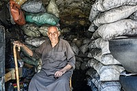 Portrait of a store owner with big walking stick selling coal for fuel in a small cave.
