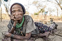 Portrait of a woman from the San tribe lying on the sandy floor of her village in a remote part of the Kalahari desert.