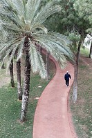 Man walking on a red path in the old Turia river bed. Valencia, Spain.