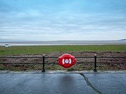 Lifebuoy on the promenade in Grange-Over-Sands looking towards estuary and Morecambe Bay, Cumbria, UK