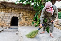 A Yezidi volunteer helps cleaning on the Lalish temples after Wednesday celebrations. Wednesday is the holy day for the practitioners of the Yezidi fa...