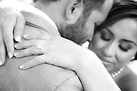 b&w close up of wedding ring bride & groom embrace