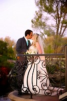 bride & groom at sunset kissing on a balcony