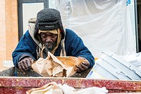 New York City, USA. Homeless African-American man searching a dumpster garbage container for left over food scraps.