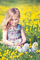 a 3 year old girl is sitting on a flower meadow.