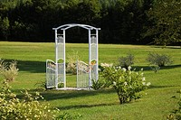 White wrought iron metal arbour gate in the middle of manicured green grass lawn in private backyard country garden in summer, Quebec, Canada. This im...