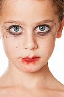 Front view of a little girl with smeared makeup on her face.