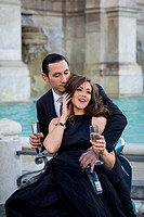 Couple toasting with a sparkling wine kissing while sitting on a vespa scooter. Janiculum water fountain. Rome, Italy.