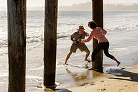 Middle aged man and woman frolicking and chasing each other around boardwalk piers at the beach.