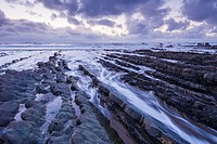 Incoming tide at dusk at Welcombe Mouth, North Devon, England.