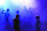 Children dancing in smoke and blue lights to music played by a disk jockey.