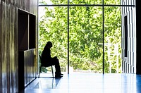 A museum guard sits quietly watching viewrs to the institution.