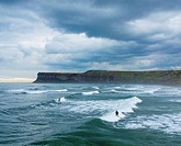 Saltburn by the Sea, North Yorkshire, England, United Kingdom. Europe. Surfers under a stormy sky at Saltburn on the North Yorkshire coast.