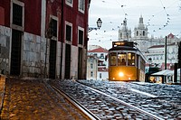 Romantic atmosphere in the old streets of Alfama with the castle in the background and tram number 28 Lisbon Portugal Europe.