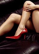 Closeup of sexy bare woman legs in red high heel shoes on a black leather couch.
