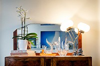 Art decó furniture, mirror, orchids, books, table lamp, decorative objects. Mahó, Minorca, Balearic Islands, Spain