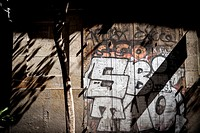 Wooden door with graffiti and shadows. Barcelona, Catalonia, Spain