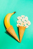 Ice-cream parlour artwork on a creative composition of ice cream waffle cones and ripe bananas on turquoise background.