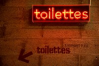 Arty original toilettes restrooms indication in red neon light