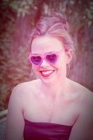 Young woman wearing heart shaped sunglasses.