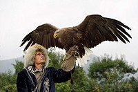 Trainer holding a White Tailed Eagle up with spread wings at Sunkar Falcon Farm Almaty Kazakhstan.