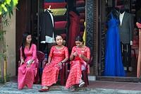 Young women tailor shop assistants wait for customers Hoi An Vietnam.