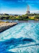 Besos river, purified water from treatment plant, in the background the chimneys of the old thermal power station, Sant Adrià del Besòs, Barcelona, ??...