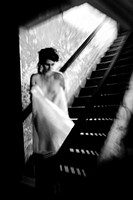 Caption: Front view of a nude 25 year old woman on a stairway, looking away from the camera, black and white.