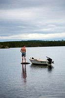 Man standing on a rock out on the lake, countryside of northern Sweden.