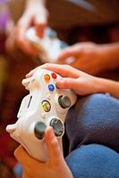 Two Boys Playing Console Game - Closeup of Fingers on Gamepad.