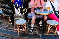 Couple of senior tourists sitting at restaurant terrace drinking beer. Montmartre, Paris, Île-de-France, France
