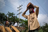 DHAKA, BANGLADESH - APRIL 30 : Bangladeshi day labors lift a heavy timber in Dhaka, Bangladesh on April 30, 2017. .
