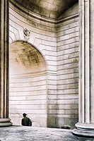 Person walks under the arch of The Bank Of England ,City of London,England.
