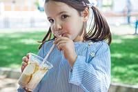 Little girl drinking milkshake at park. She is 5 years old.