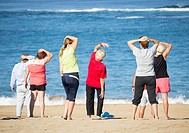 A group of elderly local women at their daily exercise class on Las Canteras beach in Las Palmas, Gran Canaria, Canary Islands, Spain.