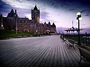 Boardwalk of Dufferin terrace and the Fairmont Le Château Frontenac castle at dusk with dramatic night sky and street lights, luxury grand hotel Chate...