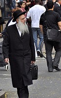 An elderly Jewish man walks down the streets of New York City