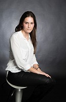 Portrait of pretty young woman with long hair in white shirt sitting on stool chair on black background.