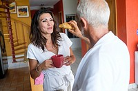 Breakfast of unequal couple - older man feeding a croissant to younger woman, Nuevo Vallarta, Nayarit, Mexico.