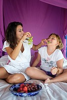 Hispanic mother and daughter having fun at eating grapes in the child's bedroom.