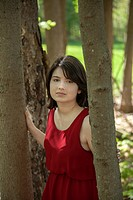 Young woman, standing by trees in a park, wearing a red dress.