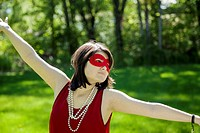 Young woman, with arms outstretched, wearing a mask, pearl necklace, and red dress in a park.
