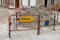 Masonry sand heap with pedestrian walk way barrier in the old quarter of medieval Berques, France.