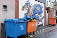 Dragon street art grafitti with orange and blue bins in Blackpool back street, England, UK.